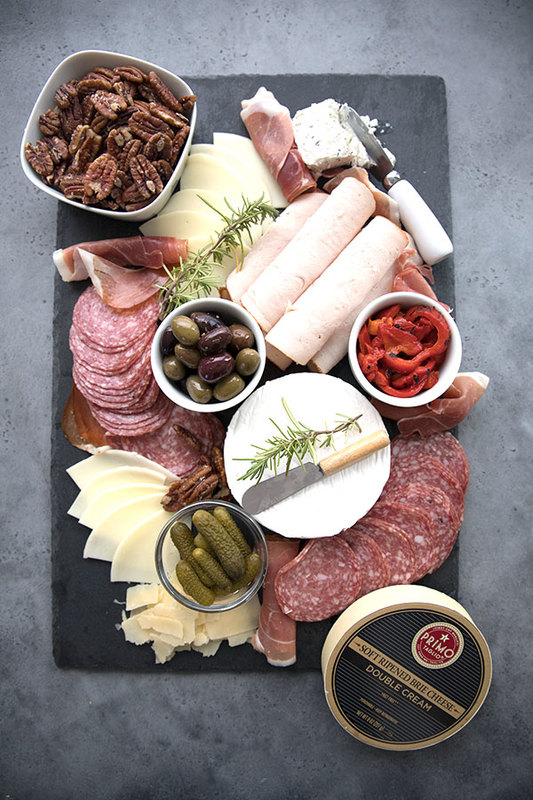 A tray of keto appetizers with meat, cheese, pecans, pickles, and olives