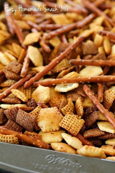 This Homemade Snack Mix Recipe is so easy to make and tastes delicious! Cereal, crackers and pretzels are tossed with a little butter and seasonings, then baked. Perfect to serve at a party or to munch on when you're watching the game. :)