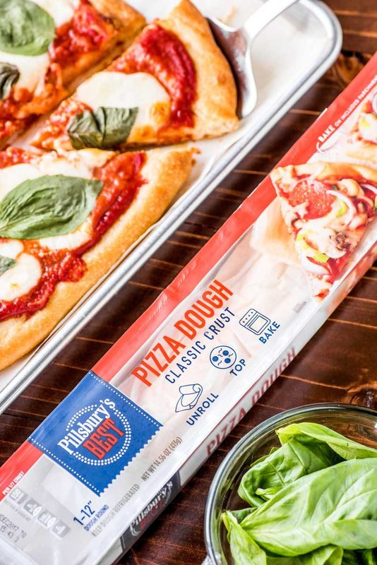 Classic Margherita Pizza! Delicious classic-crust pizza topped with crushed tomatoes, garlic, mozzarella, and basil. So simple to make and absolutely delicious! | #ad #Pillsbury @Pillsbury HomemadeHooplah.com