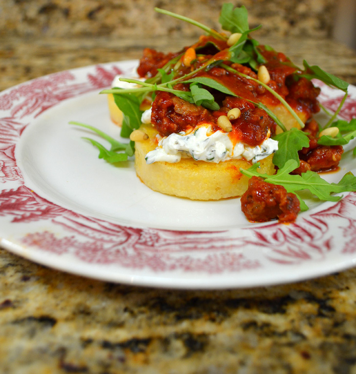 Polenta is pan fried and served with an Italian Sausage Ragu, herbed cream cheese and an arugula and tomato vinaigrette fresh salad.