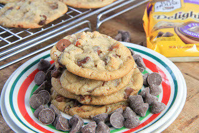 Brown Butter Chocolate Caramel Pecan Cookies served with chocolate chips inside the plate and more cookies outside of it
