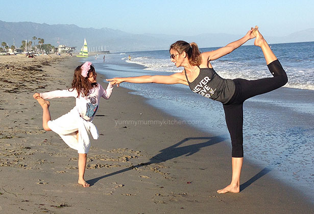 Mother and daughter doing yoga on the beach