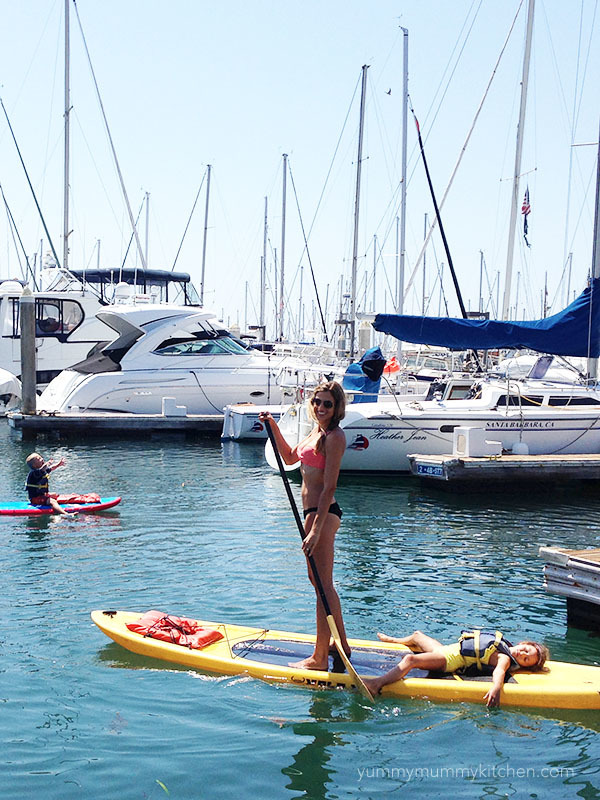 Mother and daughter on a paddle board in the Santa Barbara harbor.