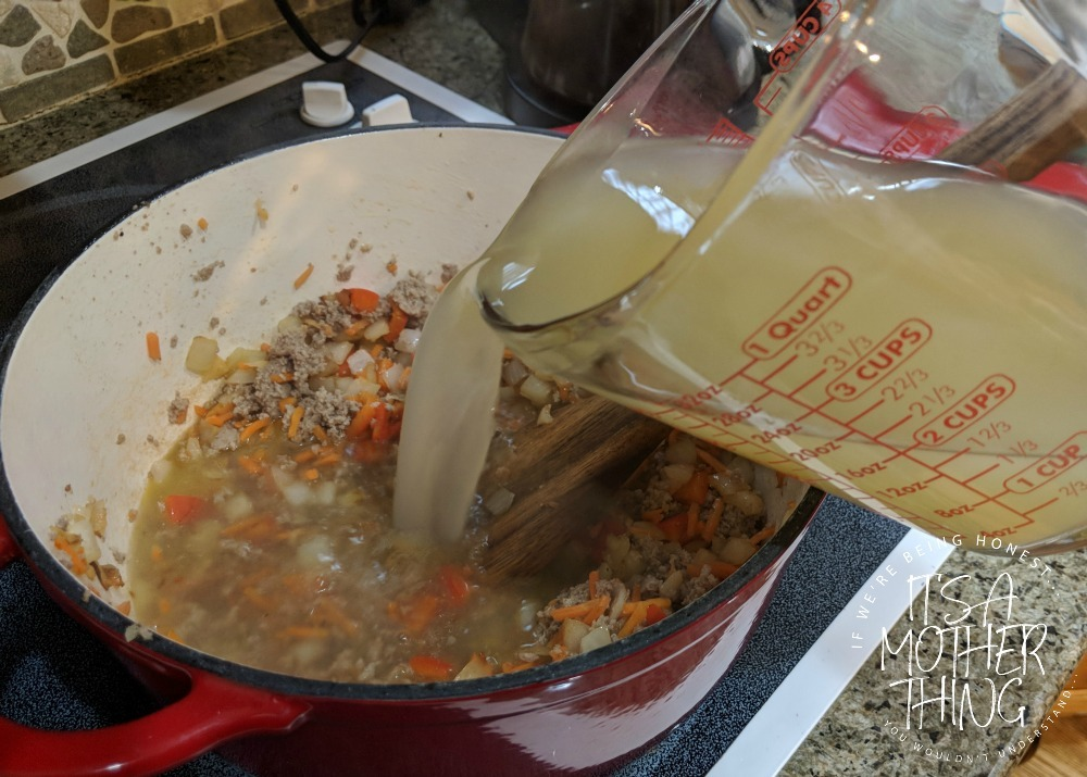 adding chicken broth into a pot