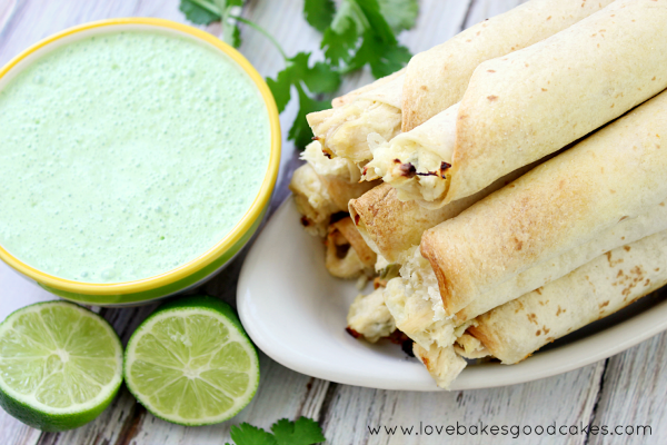 Homegating and Spicy Jalapeno Chicken Taquitos stacked up on a plate with Cilantro Lime Cream Sauce and a lime.