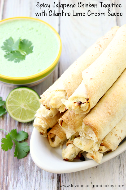 Homegating and Spicy Jalapeno Chicken Taquitos stacked up on a white dish with Cilantro Lime Cream Sauce.