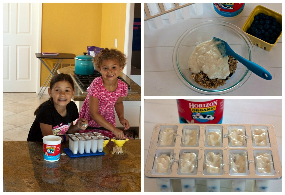 Two young girls making the yogurt parfait breakfast popsicles.