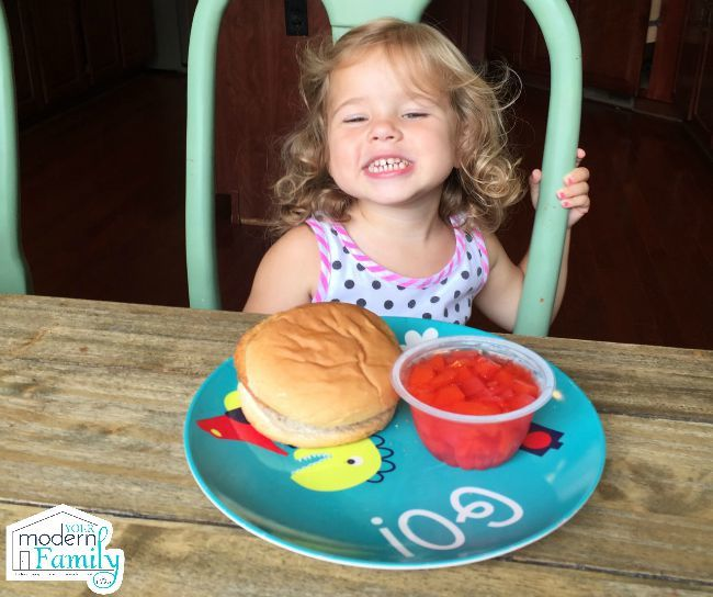 A little girl sitting at a table with a plate with a sandwich and a cup of fruit.