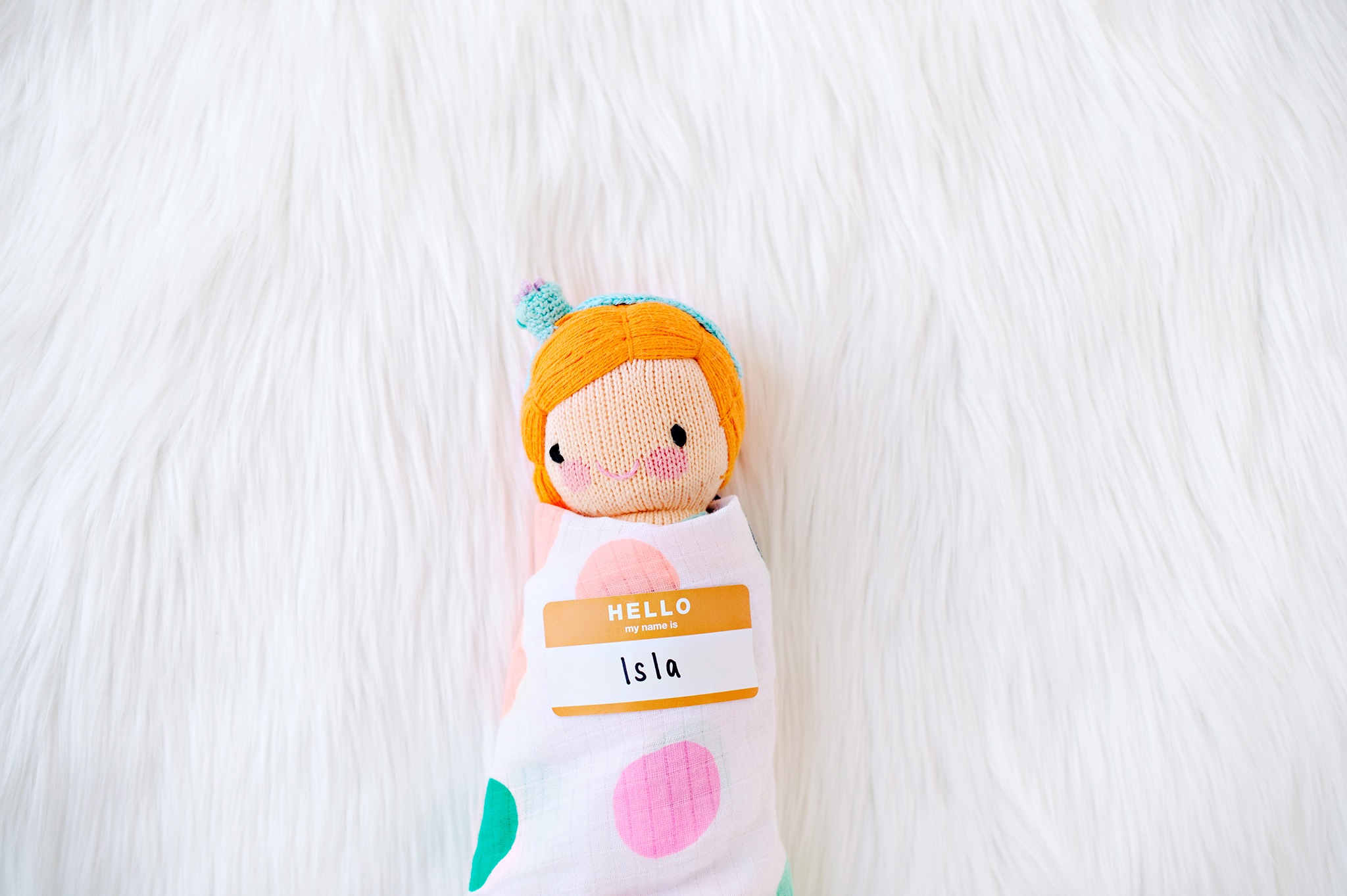 A close up of a stuffed doll wrapped in a blanket with a name tag on it.