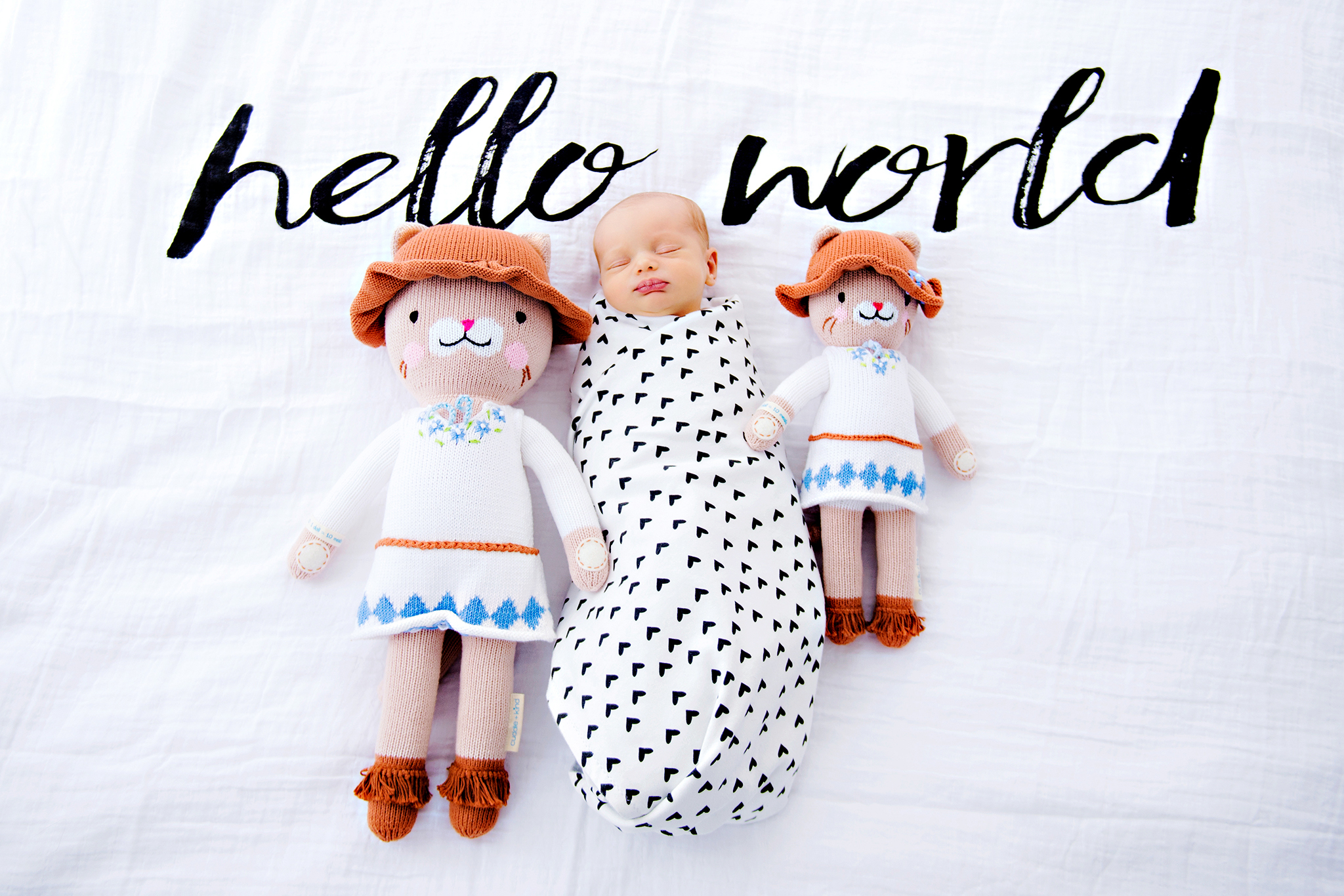 A swaddled baby with two stuffed baby dolls on each side of her with text above her.
