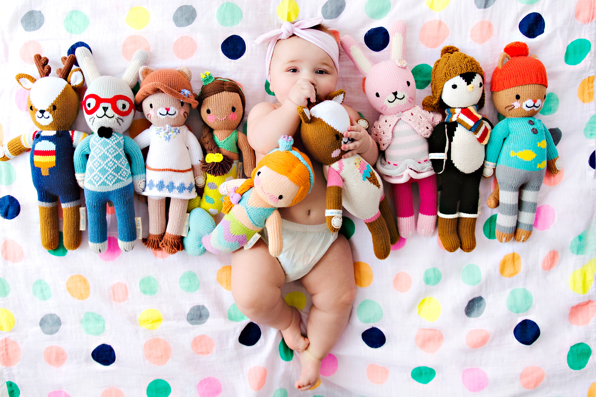 A baby lying on a blanket with numerous stuffed dolls lined up beside the baby.
