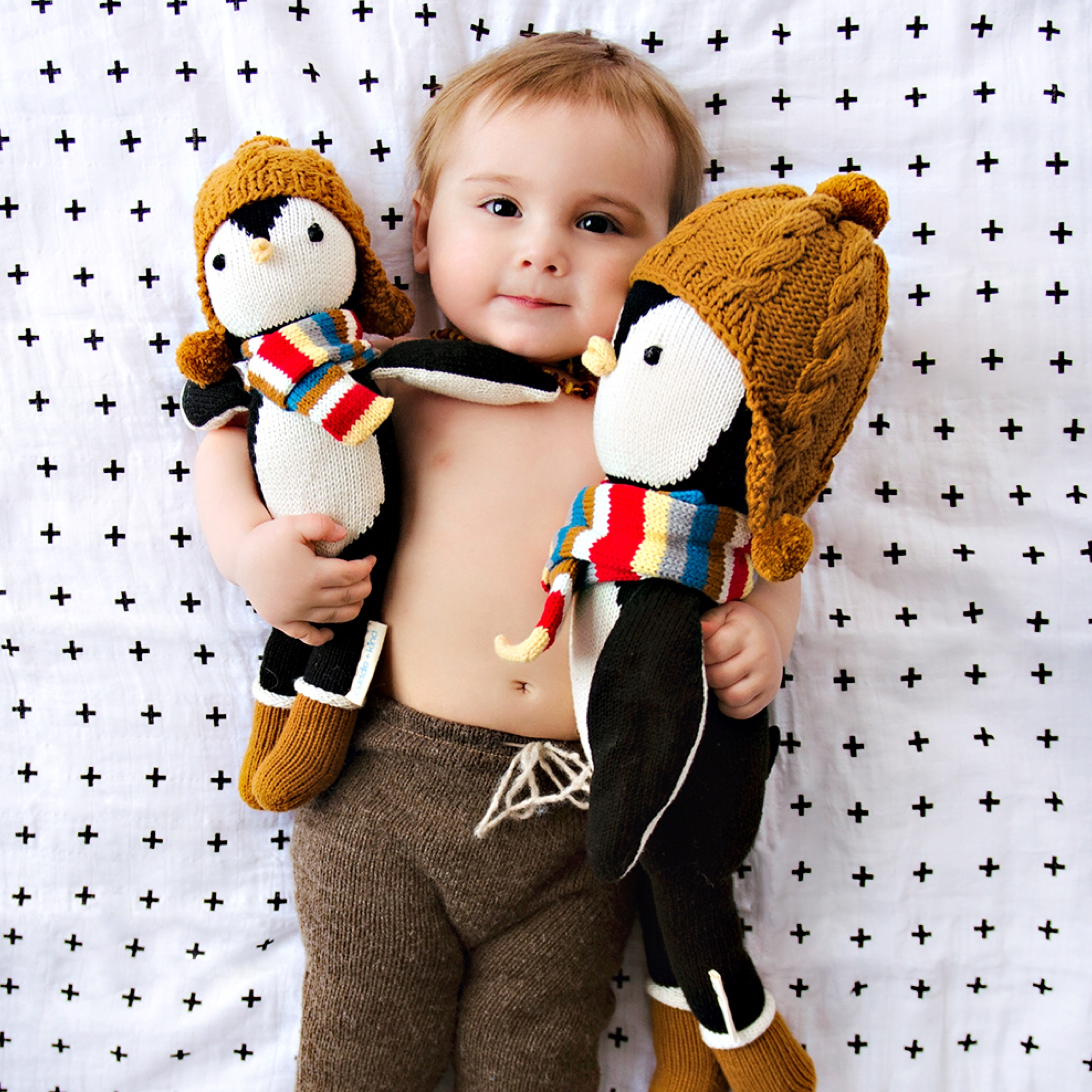 A baby holding a two stuffed animals.